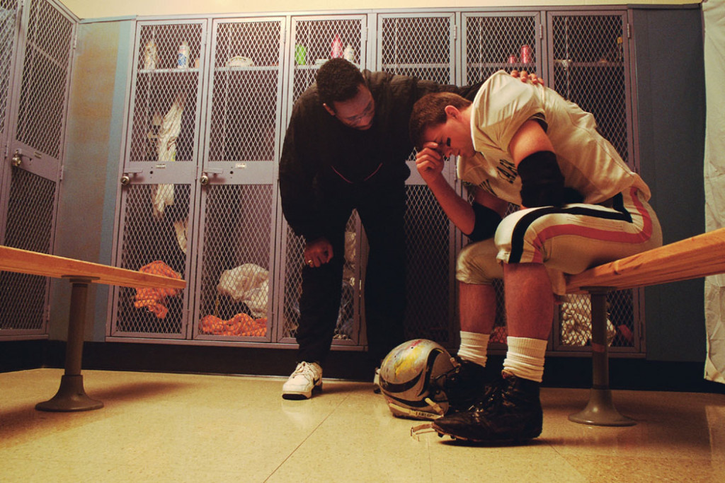 A football coach attempts to console one of his players in the locker room.