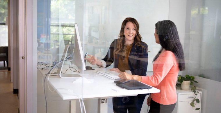 Two women talking in office next to desk