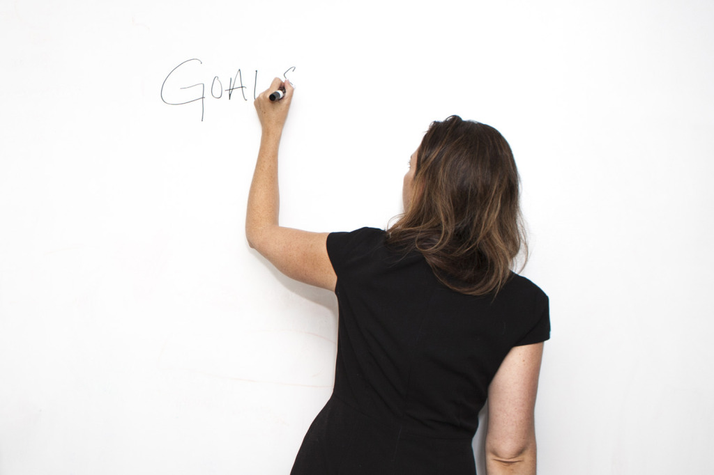 Woman Writing Goals on Board