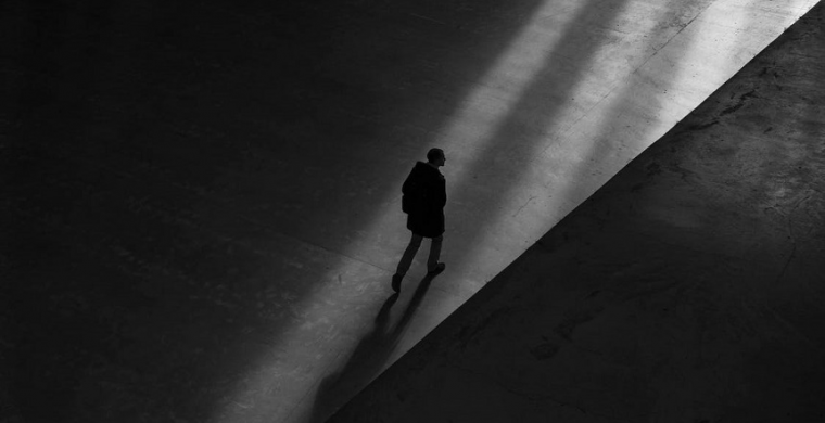 Loneliness epidemic represented by man walking alone