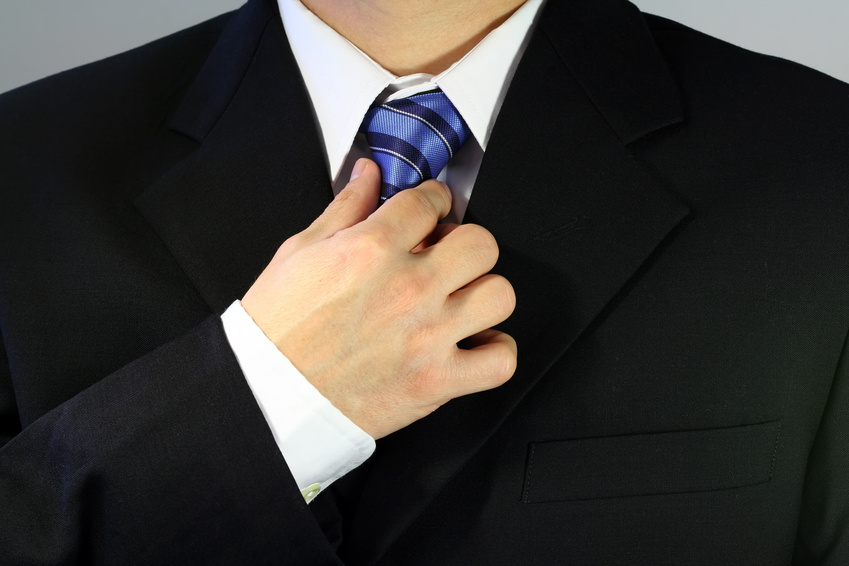 Businessman tying up his tie