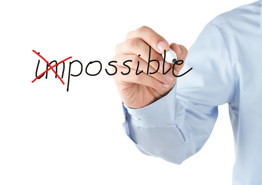 Businessman transforming word impossible into possible