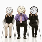 Business people holding clocks over their faces