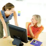 Two Young Women in Front of Computer Talking