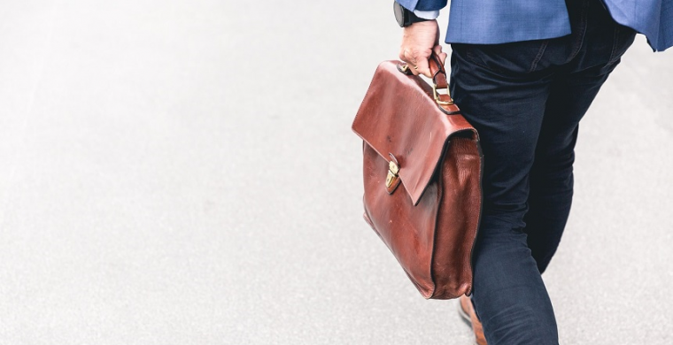Employee with brief case walking to return to office