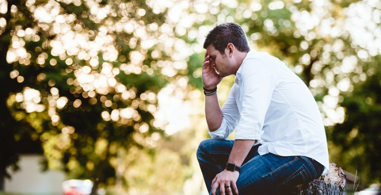 Stressed man sitting outside having a breakdown